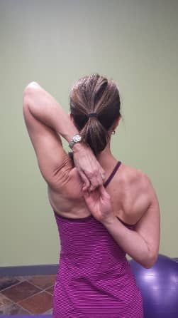 Denise demonstrating a shoulder range of motion technique. Her hands are clasped behind her back; one arm reaching over her left shoulder, one reaching up from her waist on the right-hand side.
