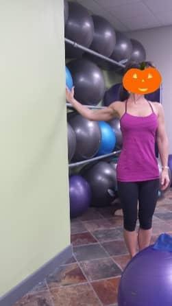Denise demonstrating Shoulder Range of Motion technique, with a pumpkin mask on her face!