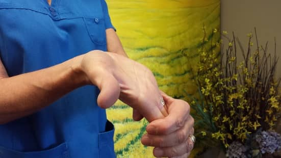 A woman demonstrates her palm being stretched