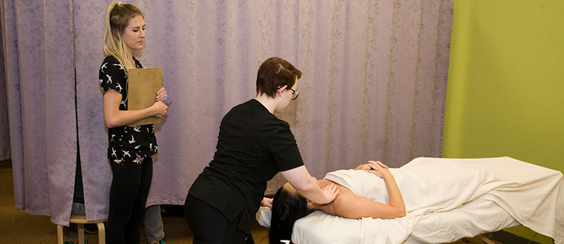 Student getting instruction on massage techniques while working on a client.