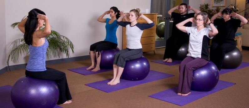 Denise leading students in a wellness course, everyone using exercise balls.