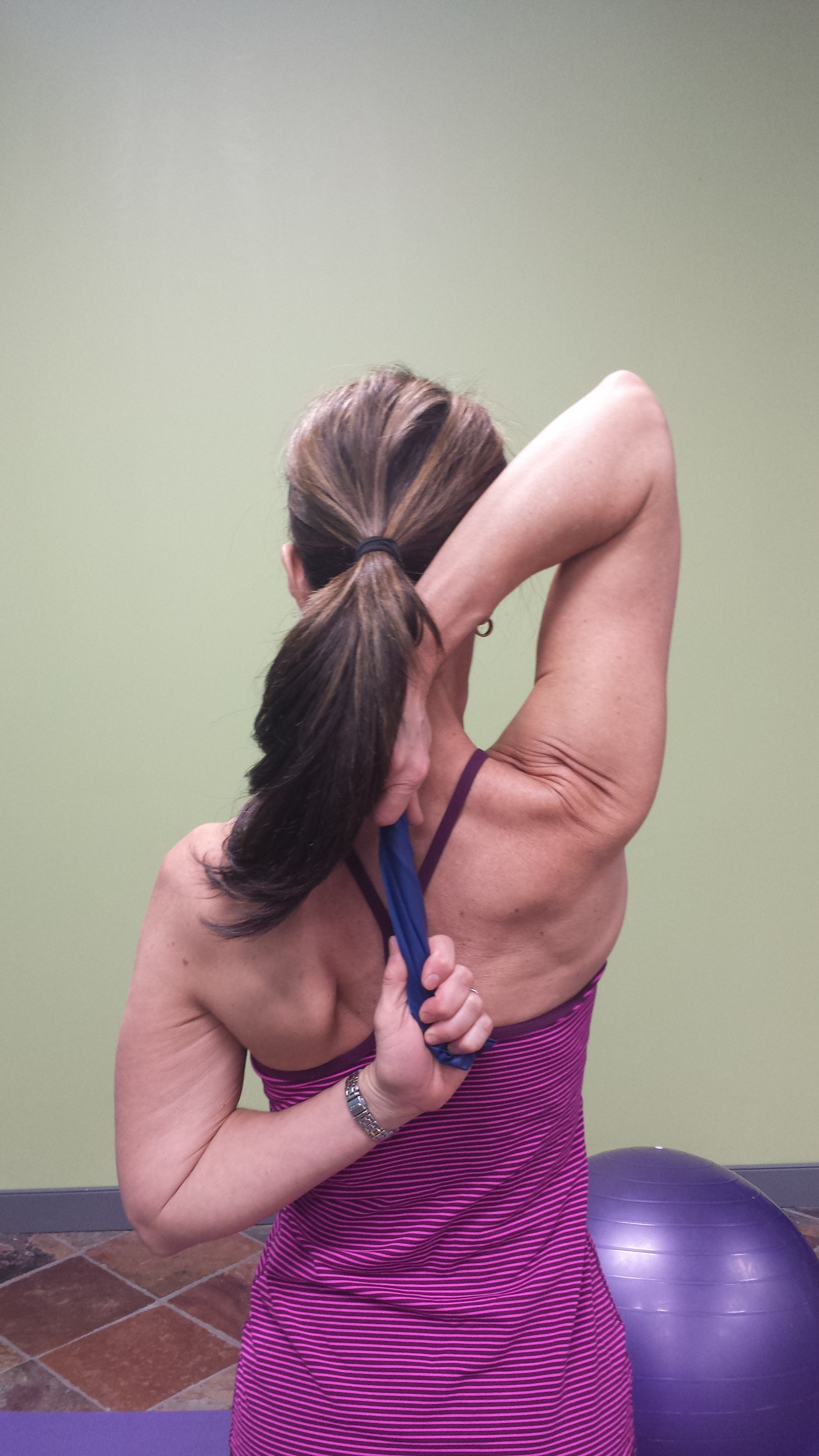 Denise demonstrating a modified shoulder range of motion technique. Her hands are behind her back; one arm reaching over her right shoulder, one reaching up from her left side waist. She is holding a band between her two hands instead of clasping her hands.