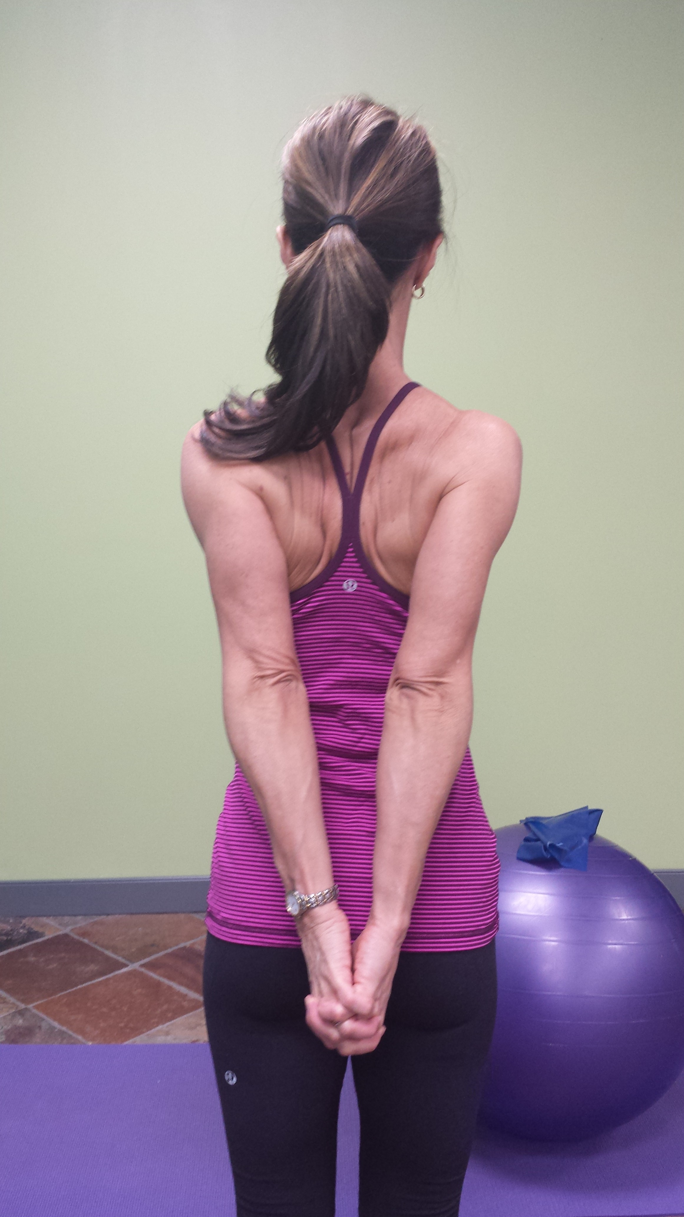 Denise demonstrating a shoulder range of motion technique, arms straight, hands clasped behind her back. This is the view from behind.