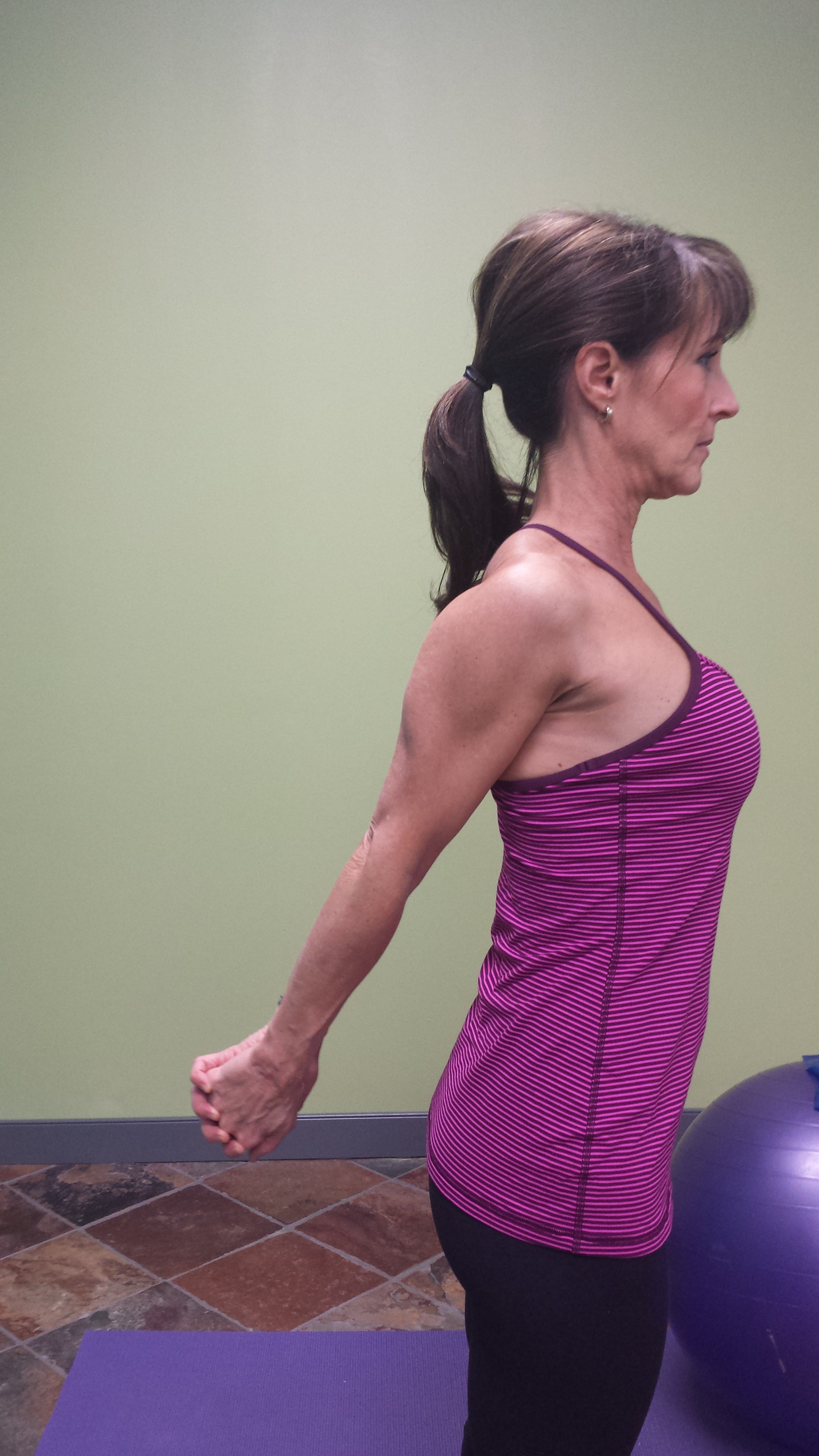 Denise demonstrating a shoulder range of motion technique, arms straight, hands clasped behind her back. This is the view from the side.